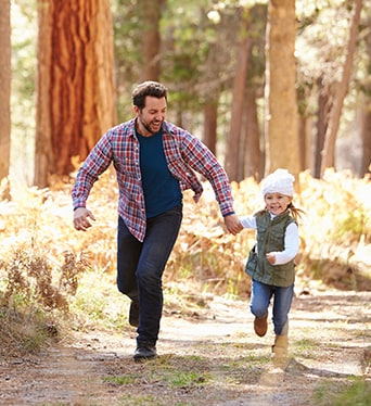 Father and daughter running in forest