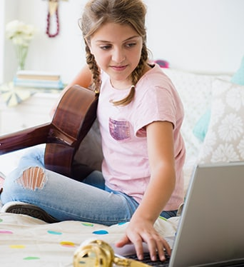 Young girl playing guitar and using laptop