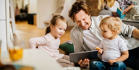 Father with two small children playing on ipad